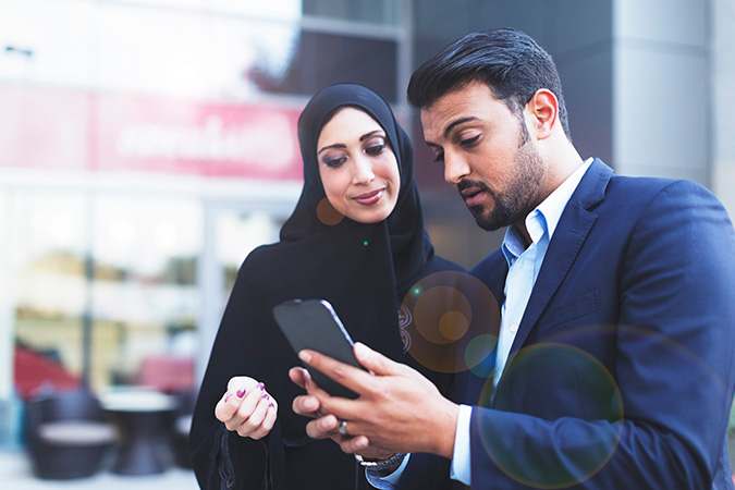 Modern Muslim couple looking at the phone
