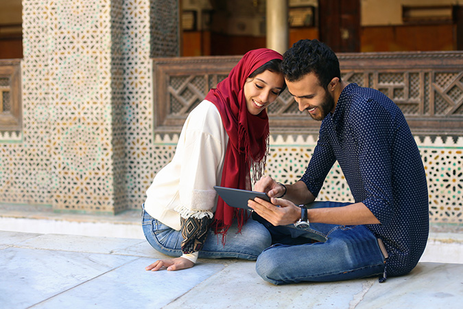 Smiling Arab couple sitting on the floor
