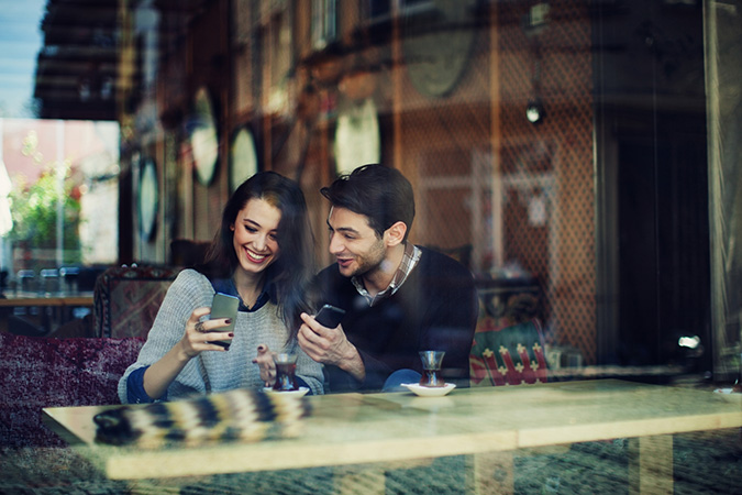 Happy Arab couple looking at the phones